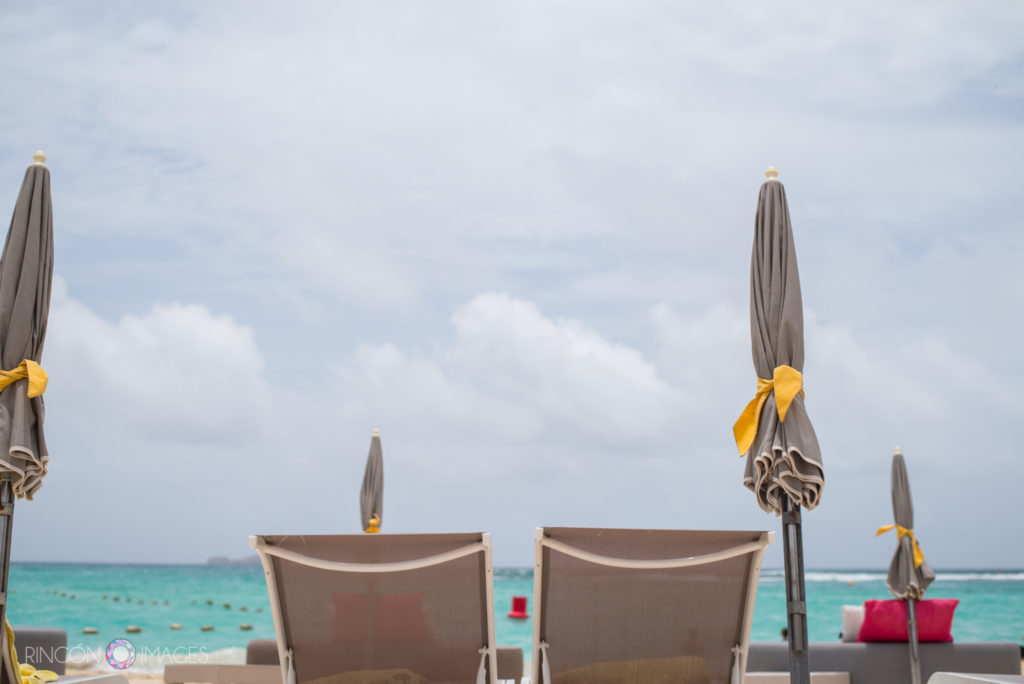 Two lounge chairs on the beach at La Plage st barths facing the turquoise ocean water.