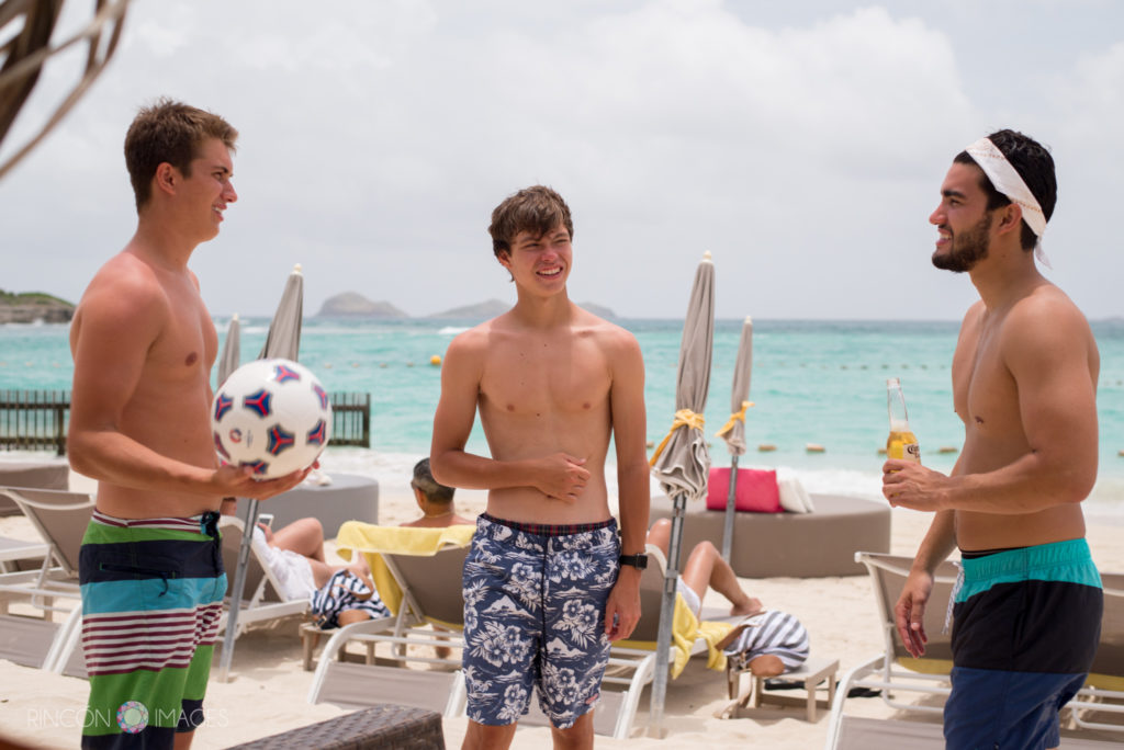 Three men talking holding a soccer ball on the beach in front of La Plage lounge chairs