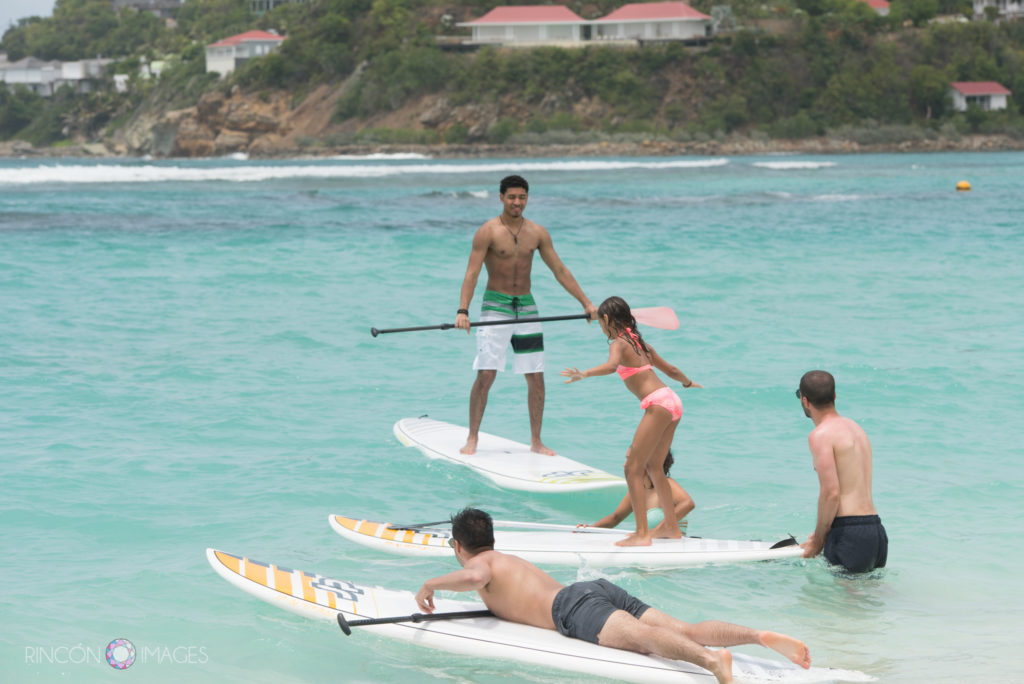 Wedding guests playing on paddle boards in the ocean on St barths island