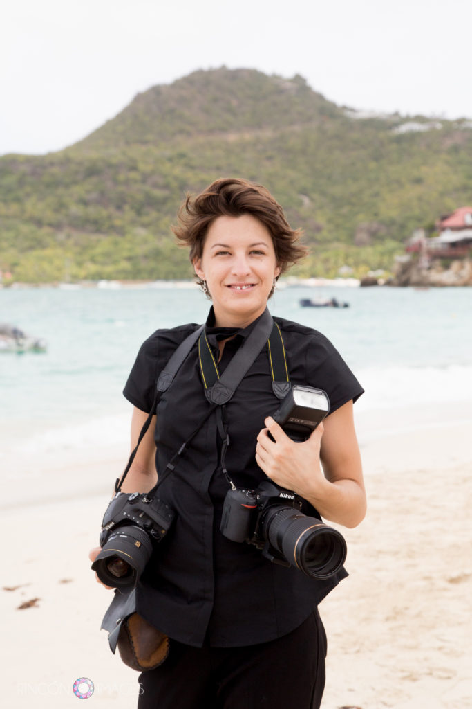 Wedding photographer wearing all black holding two cameras on the beach in St Barths