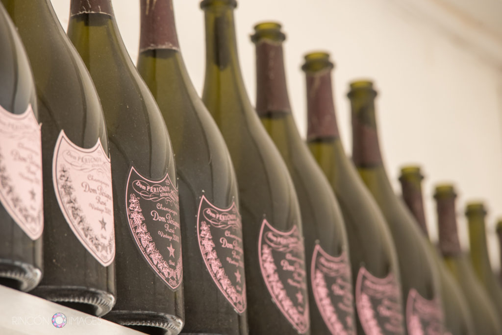 Detail photograph of green bottles of Dom Perignon champagne on a shelf