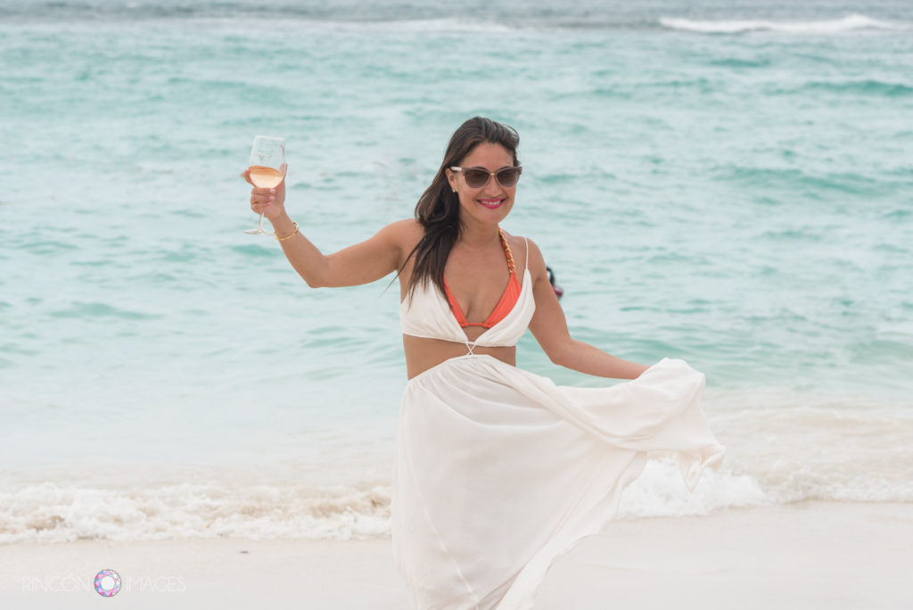Bride wearing a white beach dress with an orange bikini holding a glass of white wine on the beach in St barths.