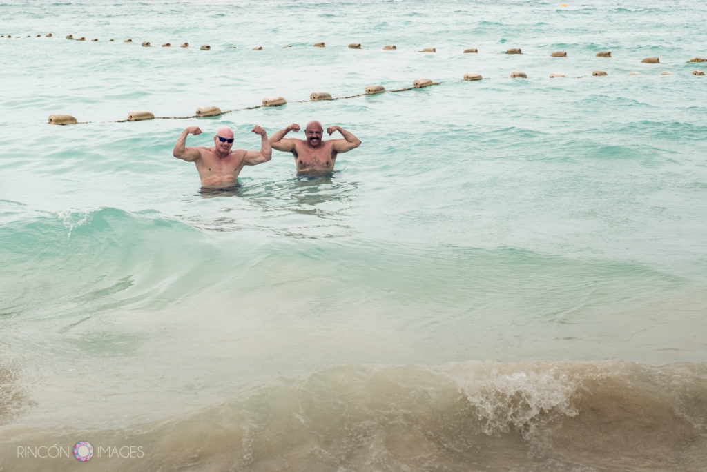 Two men flexing their arms waist deep in the ocean water in St barths.