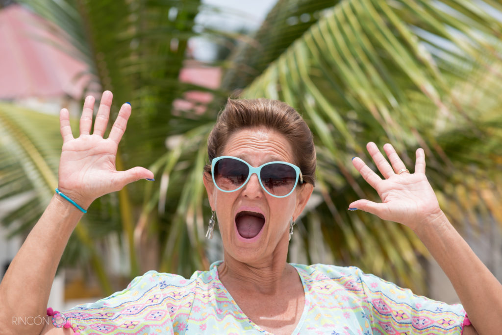 Woman holding both her hands up with a surprised expression in front of green palm trees