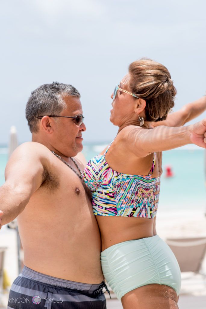 A shirtless man and a woman in a bikini chest bump on the beach