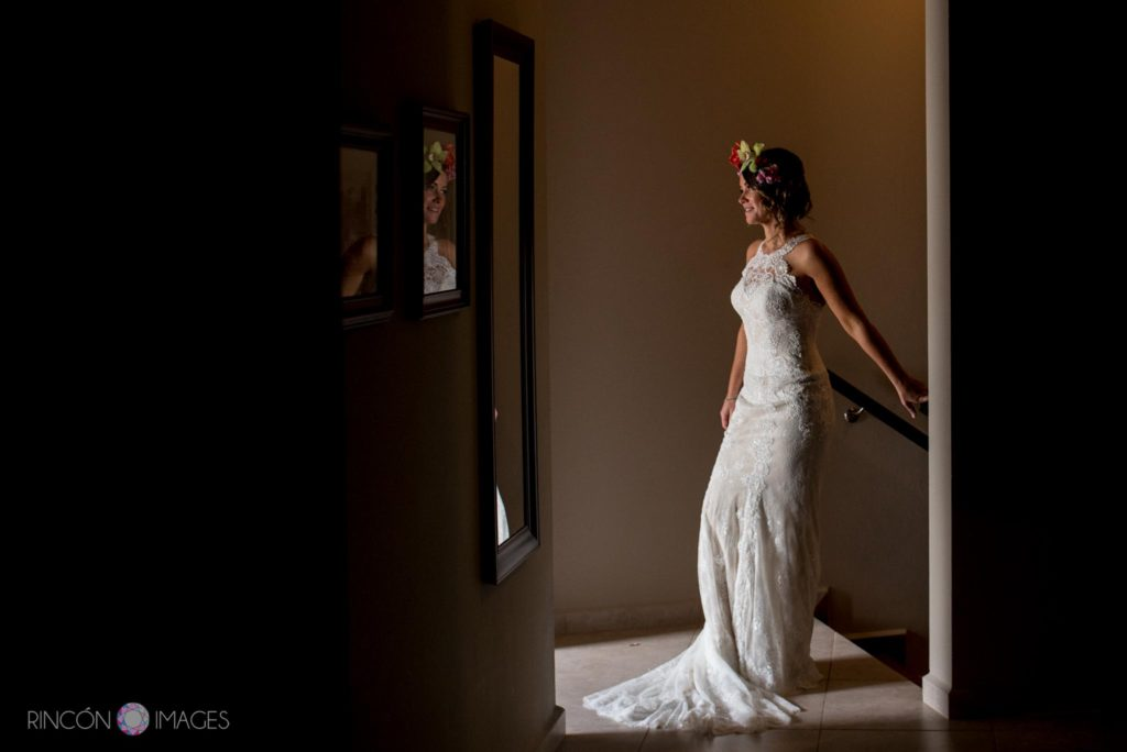 Bride standing in hallway wearing a white wedding dress with a flower crown in Rincon, Puerto Rico