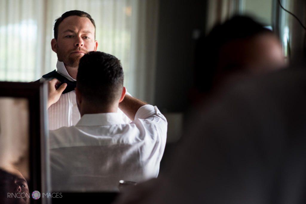 Groomsman adjusting grooms bow tie before wedding photographs