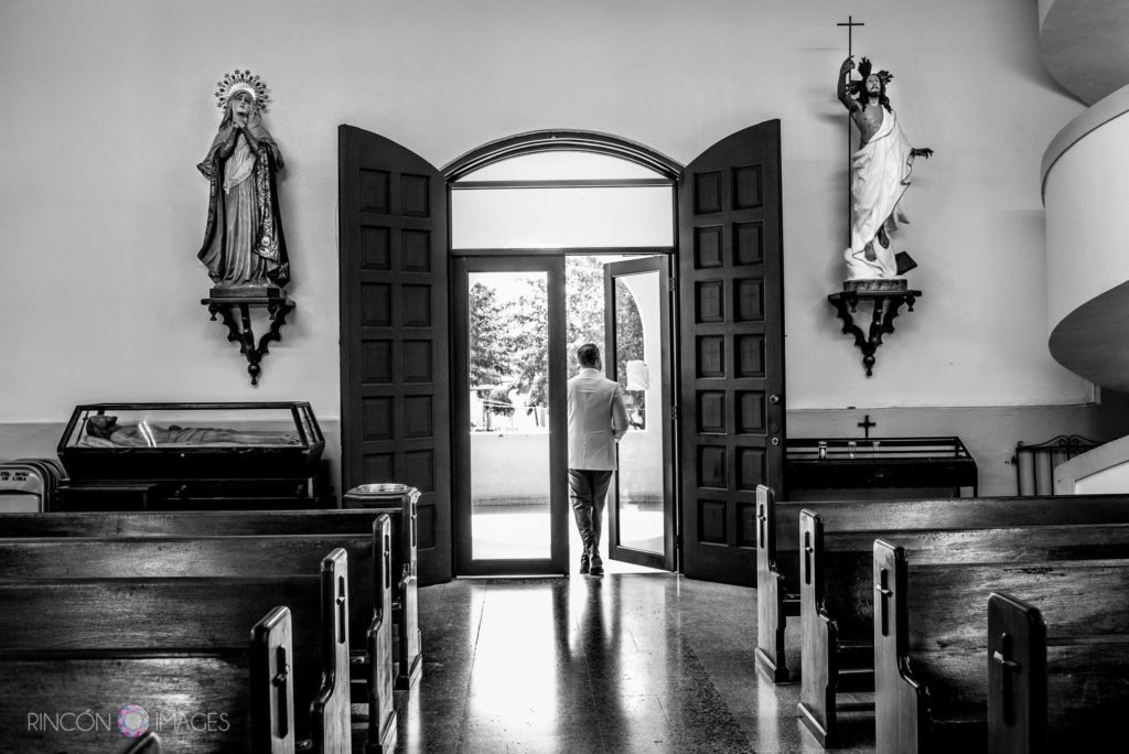Black and white wedding photograph of groom leaving the church in Rincon, Puerto Rico.