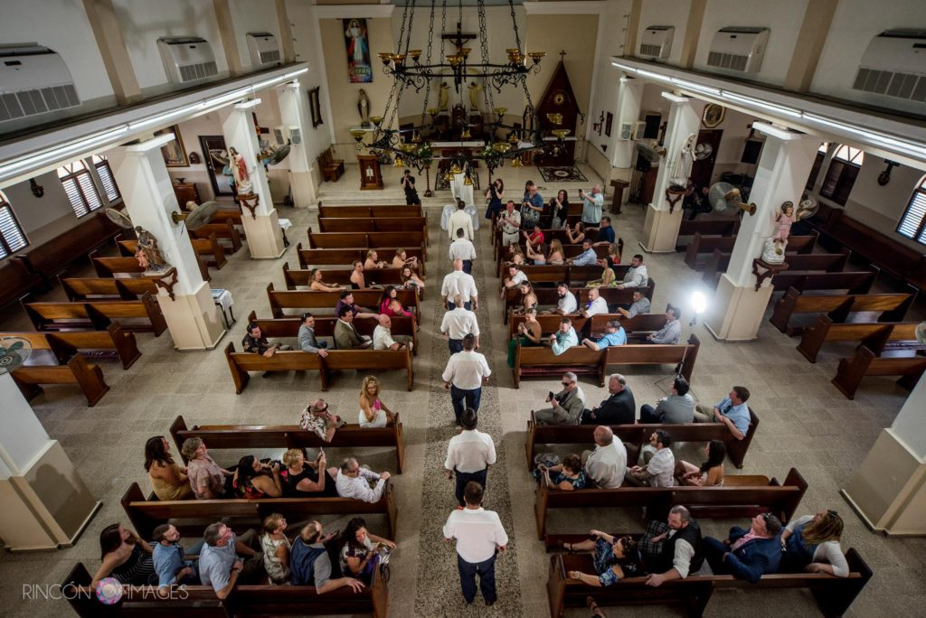 Photograph of the beginning of the wedding ceremony inside the Church in Rincon, Puerto Rico. Groomsmen walking single file into the church.