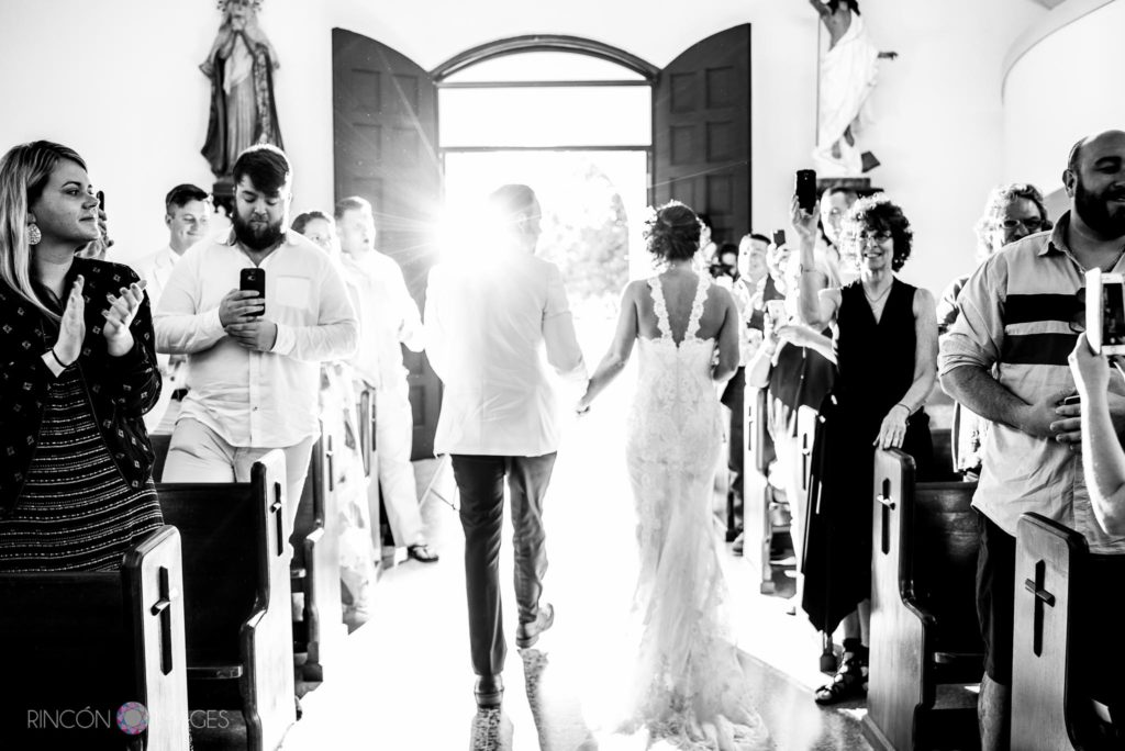 Black and white photograph of the bride and groom exiting the church after their wedding ceremony.