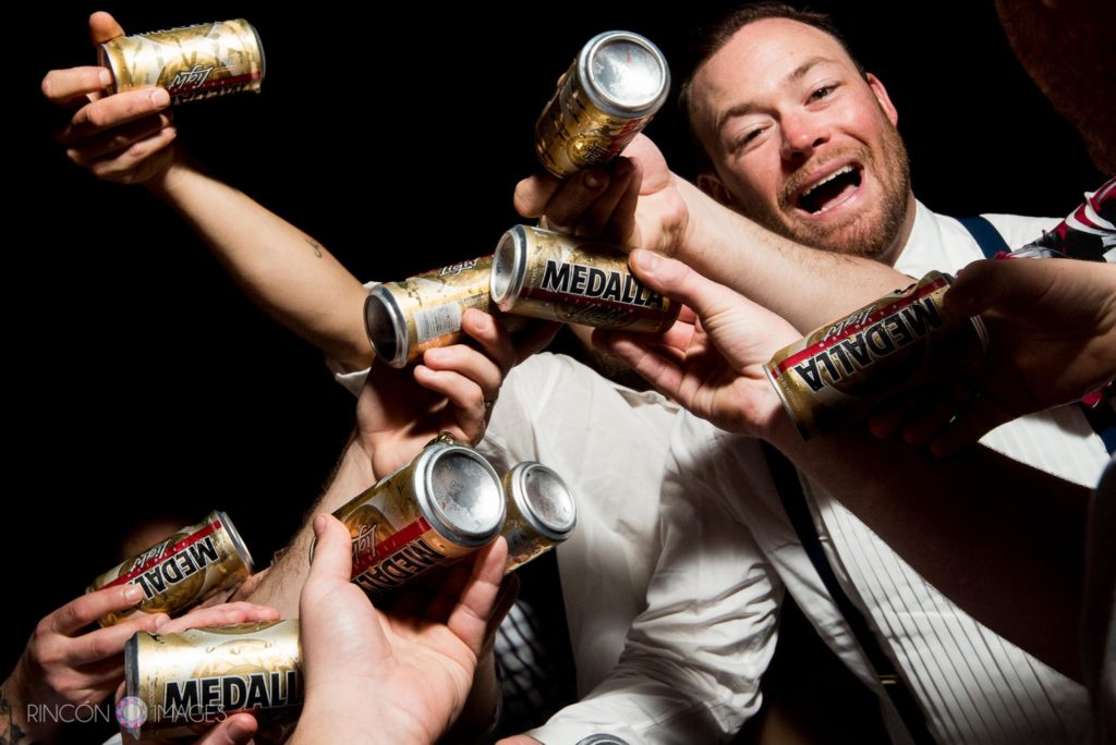 Wedding photograph of the groom surrounded by Medalla beer cans at the wedding reception in Rincon, Puerto Rico