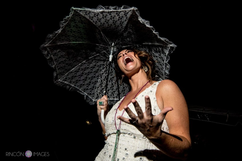 wedding photograph of the bride wearing a white dress singing while holding a white umbrella.