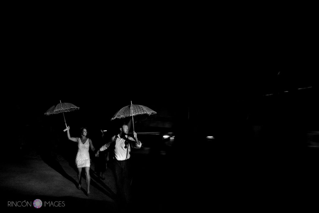 Black and white photograph of the bride and groom running while holding white umbrellas.