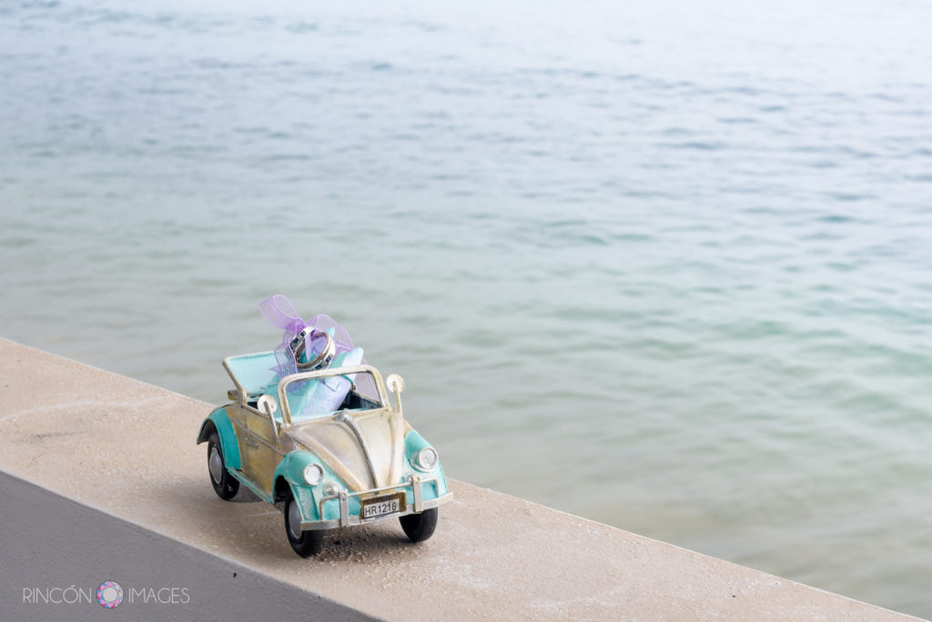 Photograph of toy Volkswagon bug with the bride and grooms wedding rings tied into the back seat. The toy is sitting on a ledge overlooking the ocean.