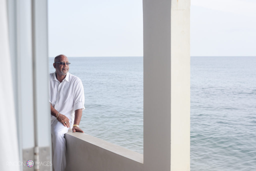 The groom sits on the edge of the porch over looking the ocean he is wearing all white clothes and sunglasses.