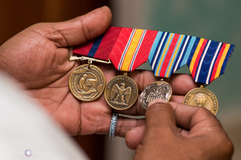 The grooms hands holding his sons marine war medals.