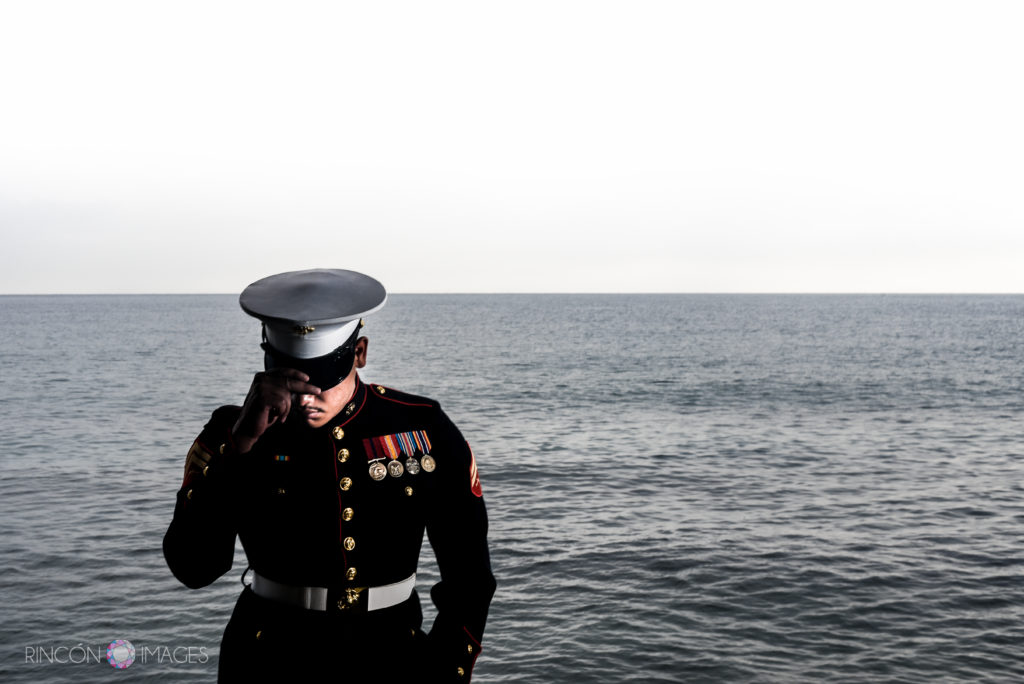 Marine wearing his uniform standing in front of the ocean tipping his hat down.