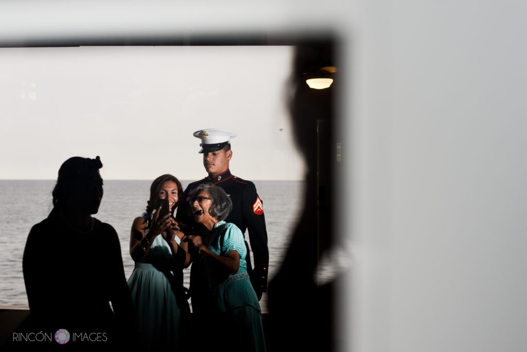 Marine stands in front of the ocean while his sister and grandmother giggle and take photographs before the wedding.