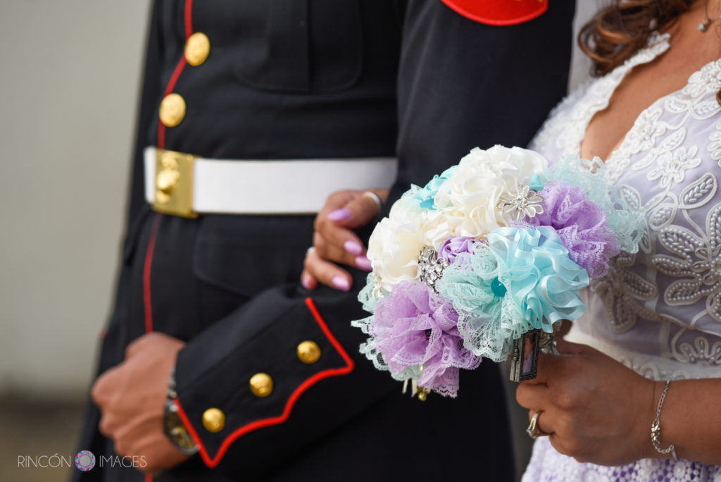 Photograph of the bride holding the arm of her son in his Marine uniform while she holds her teal and purple ribbon bouquet.