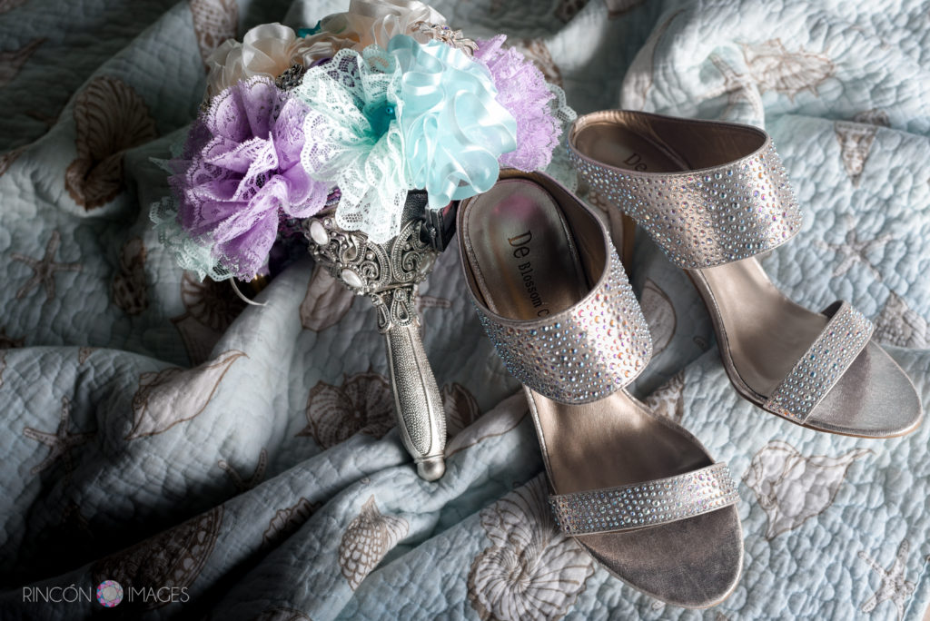 Photograph of the brides handmade purple and teal ribbon bouquet sitting next to her sequin silver wedding shoes.
