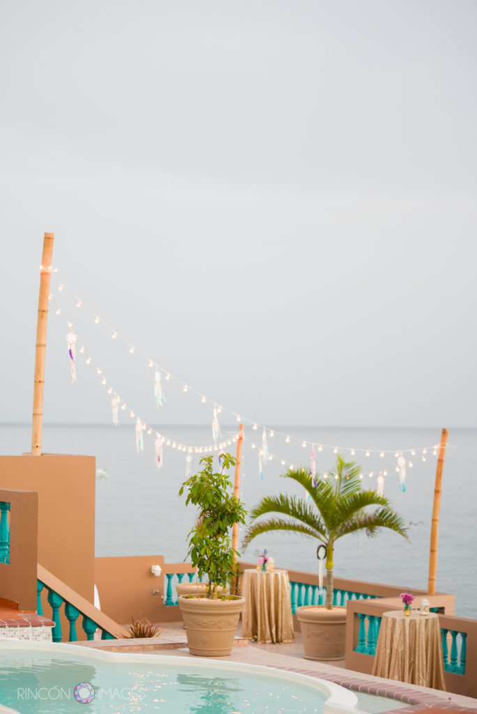 Tropical poolside wedding reception with dreamcatcher and string light decorations.