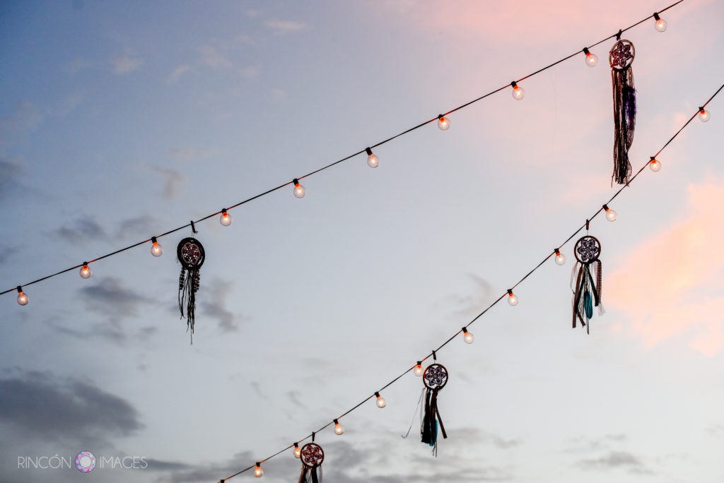 Sunset sky with silhouetted dreamcatcher decorations and outdoor string lights.