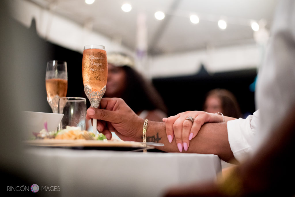 Brides hand on her grooms arm holding a glass of champagne during the wedding reception.