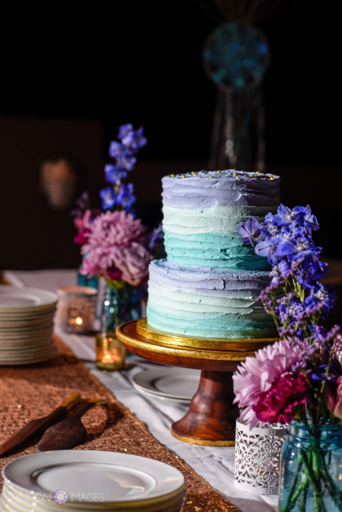 Purple and teal frosted wedding cake with purple and pink flowers on a table.