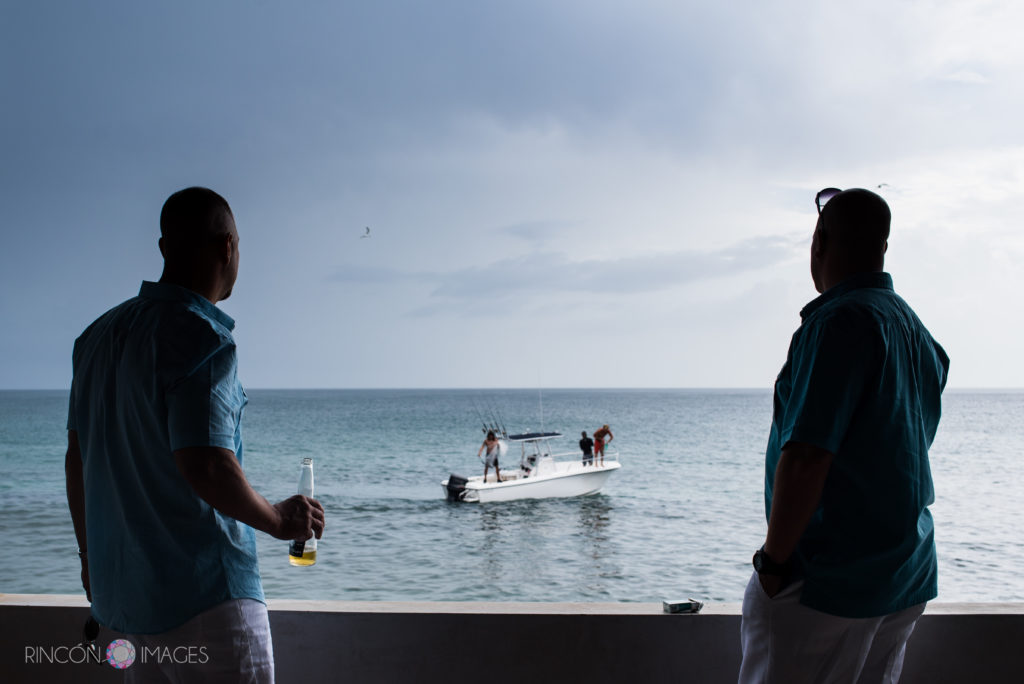 Two groomsmen wearing matching teal shirts look off the porch ledge at a fishing boat in the ocean.