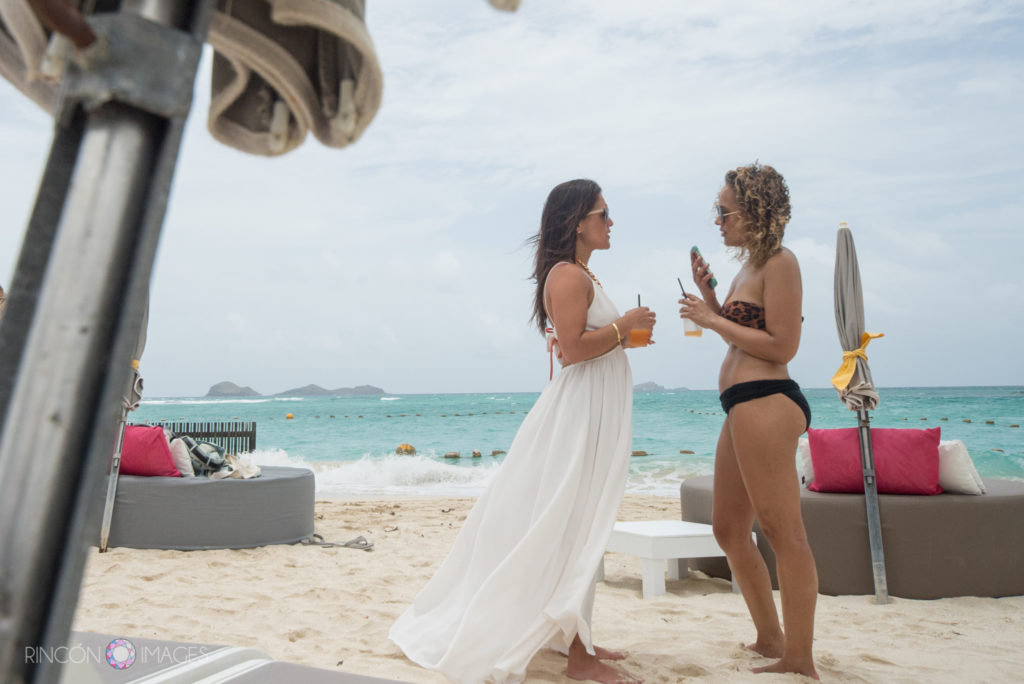 Bride in a white beach dress talking with one of her bridesmaids in a black bikini on the beach