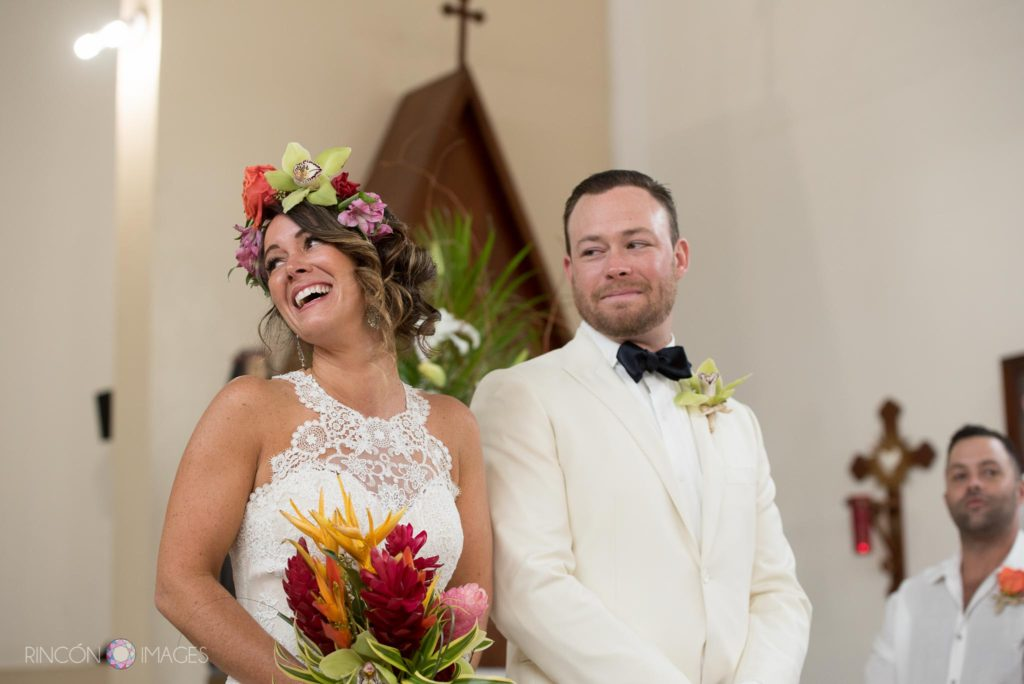 Bride laughing holding tropical flowers next to the groom at the alter during their wedding ceremony.