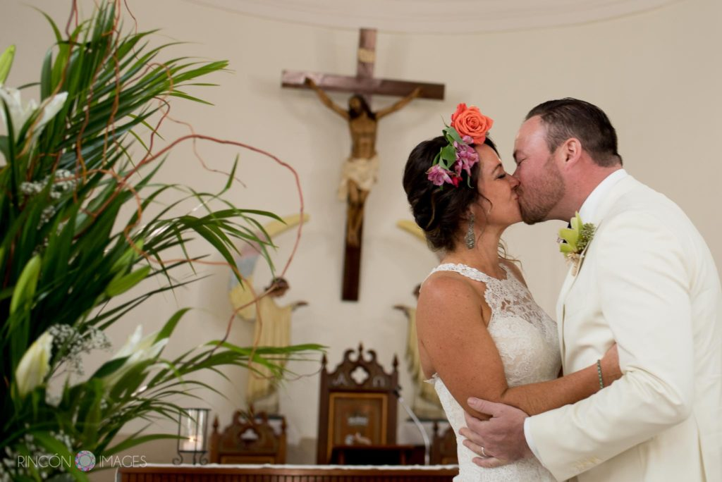 Bride and groom kiss at the end of their wedding ceremony inside the church in Rincon, Puerto Rico.