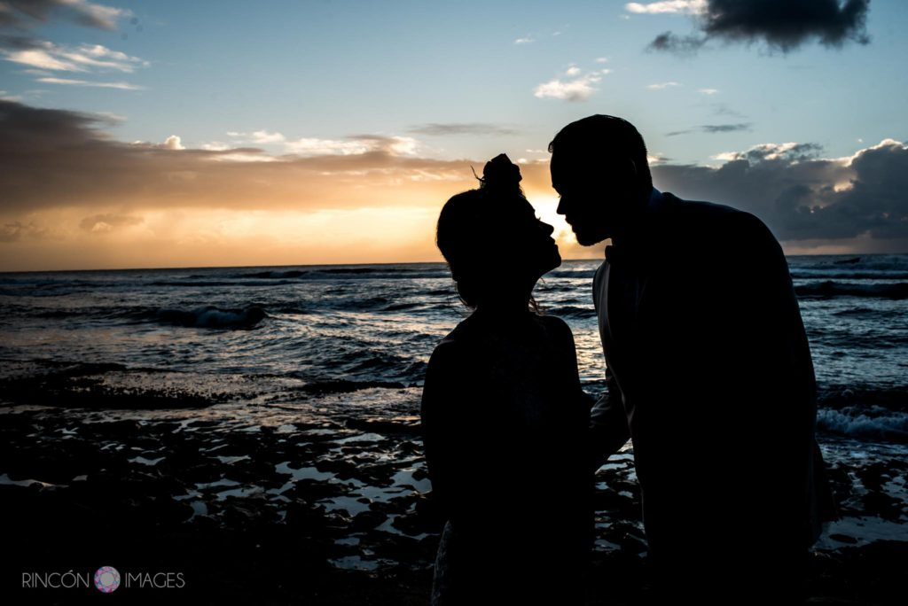 Silhouette wedding photograph of the bride and groom on the beach at sunset