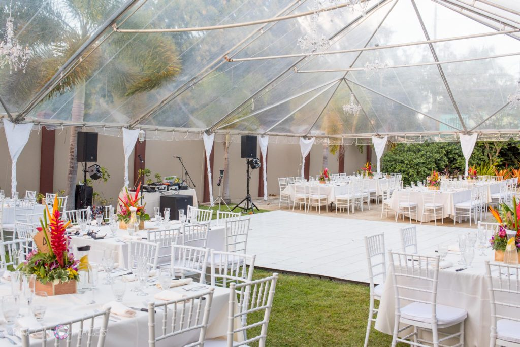 Photograph of the wedding reception area with withe tables and chairs under a tent.