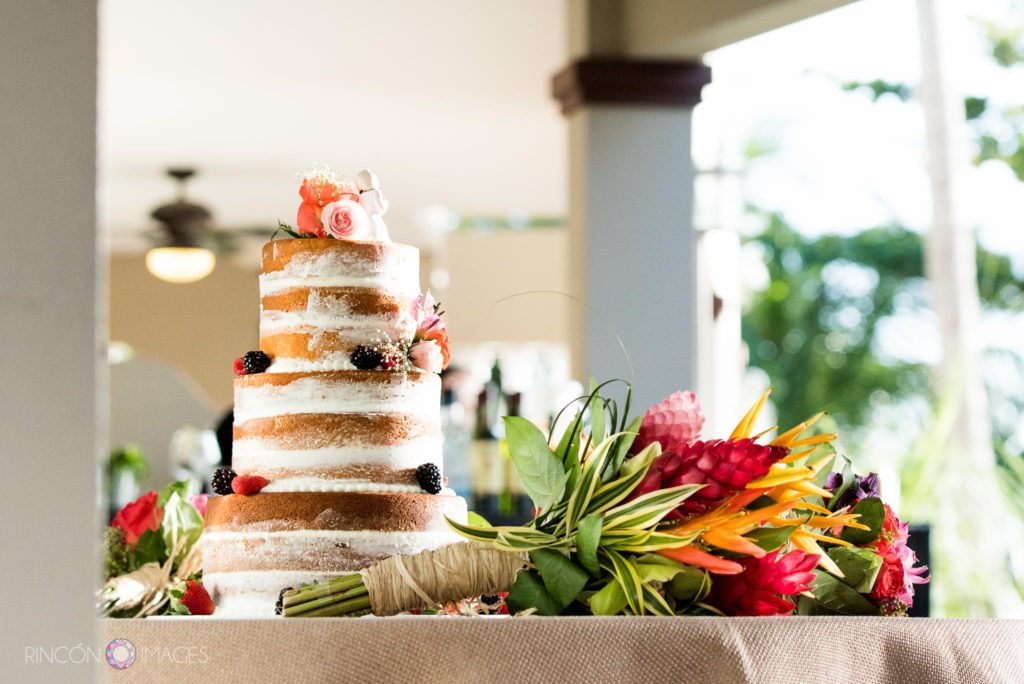 Photograph of the wedding cake with the brides tropical flower bouquet on a table.