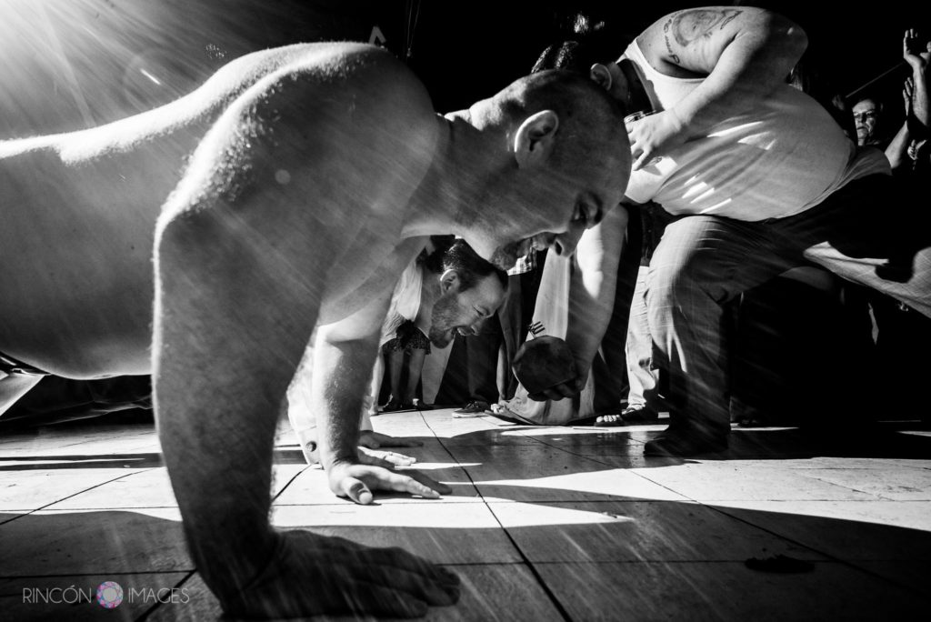 Black and white wedding photograph of the groom and his friend doing push ups on the dance floor
