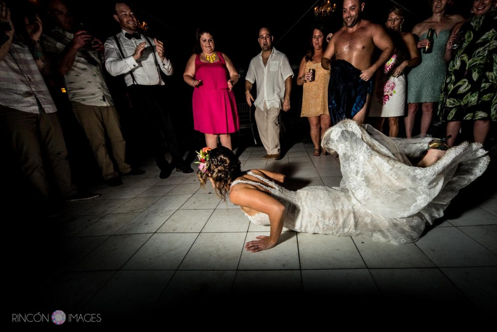 Bride wearing a white wedding dress doing the worm dance on the floor during her wedding reception